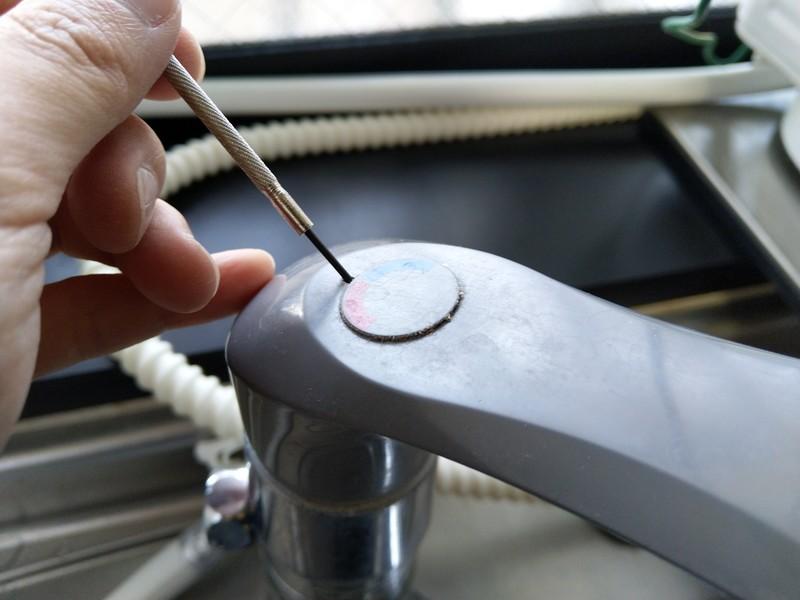 小さな穴が開いているので、精密ドライバーなどの細く硬いものを使って、てこの原理でキャップを外します。
